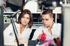 Ζεύγος των νέων σχεδιαστών που εργάζονται στο σύγχρονο γραφείο Στοκ φωτογραφίες με δικαίωμα ελεύθερης χρήσης