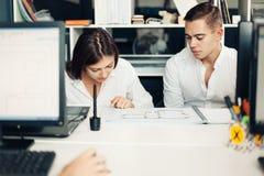 Ζεύγος των νέων σχεδιαστών που εργάζονται στο σύγχρονο γραφείο Στοκ εικόνα με δικαίωμα ελεύθερης χρήσης