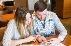 Ζεύγος των νέων σχεδιαστών που εργάζονται, δύο συνάδελφοι που συζητούν το πρόγραμμα διασκέδασης, λίγη ομάδα του businesspeople Στοκ Εικόνα