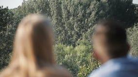 Ζεύγος των οδοιπόρων που στηρίζονται κοντά στη σκηνή στη θερμή ηλιοφάνεια Χάρτης ανάγνωσης απόθεμα βίντεο