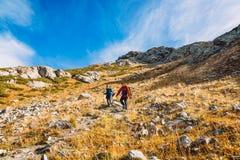 Ζεύγος των οδοιπόρων στα βουνά Οι τουρίστες κατεβαίνουν από το βουνό Στοκ Εικόνες