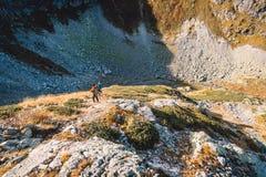 Ζεύγος των οδοιπόρων στα βουνά Οι τουρίστες κατεβαίνουν από το βουνό Ταξιδιώτες σε υπαίθριο Στοκ Εικόνες