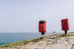 Ζεύγος των ορειβατών που περπατούν με τα μαξιλάρια συντριβής στην ακτή Στοκ εικόνα με δικαίωμα ελεύθερης χρήσης