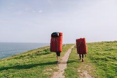 Ζεύγος των ορειβατών που περπατούν με τα μαξιλάρια συντριβής στην ακτή Στοκ Εικόνα