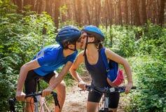 Ζεύγος των ποδηλατών που φιλούν στο δάσος Στοκ Φωτογραφία