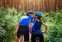 Ζεύγος των ποδηλατών που φιλούν στο δάσος Στοκ Φωτογραφίες