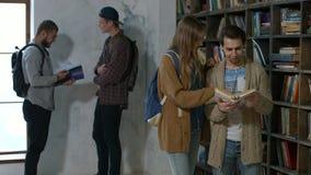 Ζεύγος των σπουδαστών που διαβάζουν το βιβλίο στη βιβλιοθήκη κολλεγίων απόθεμα βίντεο