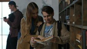 Ζεύγος των σπουδαστών που μαθαίνουν μαζί στη βιβλιοθήκη απόθεμα βίντεο