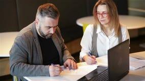 Ζεύγος των συναδέλφων που εργάζονται μαζί στο γραφείο Εργαζόμενος δύο επιχειρήσεων που προετοιμάζει το νέο πρόγραμμα για το lap-t απόθεμα βίντεο