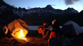 Ζεύγος των ταξιδιωτών στο σούρουπο κοντά σε μια πυρά προσκόπων απόθεμα βίντεο