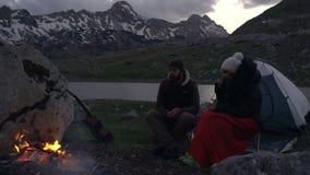 Ζεύγος των ταξιδιωτών στο σούρουπο κοντά σε μια πυρά προσκόπων φιλμ μικρού μήκους