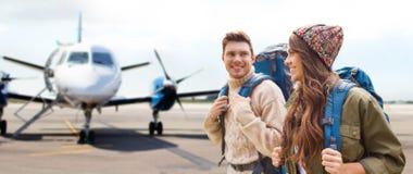 Ζεύγος των τουριστών με τα σακίδια πλάτης πέρα από το αεροπλάνο στοκ εικόνες