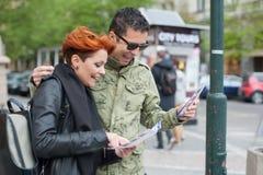 Ζεύγος των τουριστών που εξετάζουν τον οδηγό πόλεων στοκ φωτογραφία