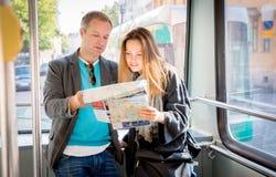 Ζεύγος των τουριστών που διαβάζουν το χάρτη πόλεων, που οδηγά το τραμ Στοκ Φωτογραφία