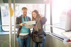 Ζεύγος των τουριστών που διαβάζουν το χάρτη πόλεων, που οδηγά το τραμ Στοκ φωτογραφία με δικαίωμα ελεύθερης χρήσης
