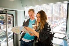 Ζεύγος των τουριστών που διαβάζουν το χάρτη πόλεων, που οδηγά το τραμ Στοκ εικόνες με δικαίωμα ελεύθερης χρήσης
