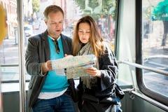 Ζεύγος των τουριστών που διαβάζουν το χάρτη πόλεων, που οδηγά το τραμ Στοκ Εικόνες