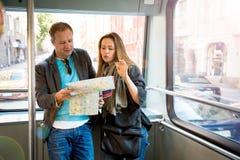 Ζεύγος των τουριστών που διαβάζουν το χάρτη πόλεων, που οδηγά το τραμ Στοκ εικόνα με δικαίωμα ελεύθερης χρήσης