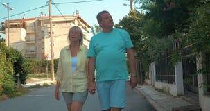 Ζεύγος των τουριστών που περπατούν κατά μήκος του διπλανού δρόμου φιλμ μικρού μήκους