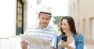 Ζεύγος των τουριστών που περπατούν συγκρίνοντας το τηλέφωνο και το χάρτη απόθεμα βίντεο