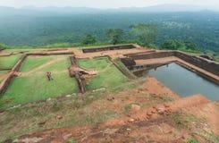 Ζεύγος των τουριστών που προσέχουν τις καταστροφές της αρχαίας πόλης Sigiriya με τη λίμνη νερού και τη archeological περιοχή Στοκ φωτογραφία με δικαίωμα ελεύθερης χρήσης
