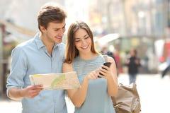 Ζεύγος των τουριστών που συμβουλεύονται ένα ΠΣΤ οδηγών και smartphone πόλεων