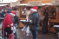 Ζεύγος των τουριστών που χαμογελούν με τα καπέλα Χριστουγέννων στην αγορά Χριστουγέννων Στοκ φωτογραφίες με δικαίωμα ελεύθερης χρήσης