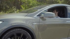 Ζεύγος των φίλων που μιλούν μέσα για την οδήγηση του γκρίζου αυτοκινήτου απόθεμα βίντεο