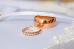 Ζεύγος των χρυσών δαχτυλιδιών γαμήλιων διαμαντιών στο γαμήλιο μαξιλάρι Στοκ Εικόνα
