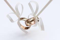Ζεύγος των χρυσών γαμήλιων δαχτυλιδιών με τα τόξα Στοκ φωτογραφία με δικαίωμα ελεύθερης χρήσης