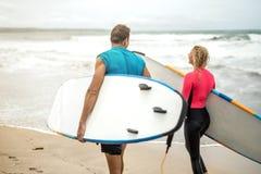 Ζεύγος των surfers στην ωκεάνια ακτή ` s Στοκ εικόνα με δικαίωμα ελεύθερης χρήσης
