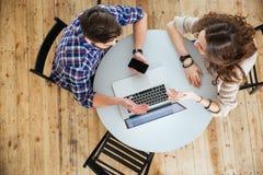 Ζεύγος χρησιμοποιώντας το lap-top και κρατώντας το κενό κινητό τηλέφωνο οθόνης στον καφέ Στοκ εικόνα με δικαίωμα ελεύθερης χρήσης