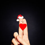 ζεύγος Χριστουγέννων Ευτυχή δάχτυλα ζεύγους στο καπέλο Santa Στοκ Φωτογραφία