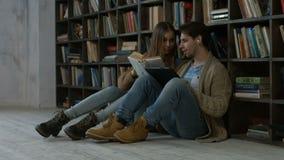Ζεύγος Hipster που μαθαίνει μαζί στη βιβλιοθήκη απόθεμα βίντεο