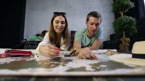 Ζεύγος Hipster που τοποθετεί τις καρφίτσες στο χάρτη ταξιδιού γρατσουνιών απόθεμα βίντεο