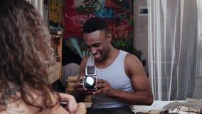 Ζεύγος Multiethnic στο κρεβάτι το πρωί Ο νέος όμορφος άνδρας που παίρνει τις φωτογραφίες στο παλαιό photocamera, γυναίκα θέτει απόθεμα βίντεο