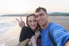 Ζεύγος Selfie ερωτευμένο στην παραλία στο ηλιοβασίλεμα με ένα σύμβολο της ειρήνης Στοκ Εικόνες