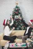 Ζεύγος Youn στην κόκκινη συνεδρίαση καπέλων στον καναπέ μεταξύ των χριστουγεννιάτικων δέντρων α στοκ φωτογραφίες