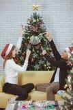 Ζεύγος Youn στην κόκκινη συνεδρίαση καπέλων στον καναπέ μεταξύ των χριστουγεννιάτικων δέντρων α στοκ φωτογραφία