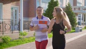 Ζεύγους στην οδό Τρέξιμο στην πόλη Άνδρας και γυναίκα που κάνουν τον αθλητισμό απόθεμα βίντεο