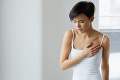 Ζητήματα υγείας Όμορφη γυναίκα που αισθάνεται τον ισχυρό πόνο στο στήθος Στοκ Φωτογραφία