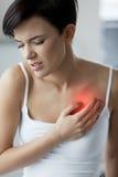 Ζητήματα υγείας Όμορφη γυναίκα που αισθάνεται τον ισχυρό πόνο στο στήθος στοκ εικόνες