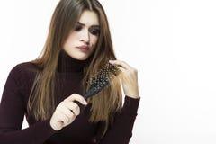 Ζητήματα Hairloss και φαλάκρας Νέο καυκάσιο θηλυκό που έχει τα προβλήματα τρίχας Έλεγχος της τρίχας στη βούρτσα γηα τα μαλλιά στοκ εικόνα