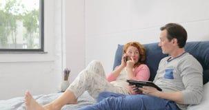 Ζηλότυπος άνδρας που εξετάζει την ομιλία γυναικών στη συνεδρίαση γέλιου τηλεφωνήματος κυττάρων στο κρεβάτι στην κρεβατοκάμαρα ζεύ απόθεμα βίντεο