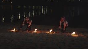 Ζογκλέρ θηλυκών που αυξάνουν τους αναμμένους φανούς που βρίσκονται στην άμμο απόθεμα βίντεο