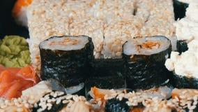 Ζουμ καμερών Πολλά διαφορετικά σούσια Nigiri Gunkan Maki με το αγγούρι τυριών της Φιλαδέλφειας σολομών χελιών κλείνουν επάνω την  απόθεμα βίντεο