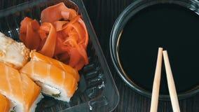 Ζουμ καμερών Το Stylishly έβαλε τα σούσια που τέθηκαν σε ένα μαύρο ξύλινο υπόβαθρο δίπλα στη σάλτσα σόγιας και τα κινεζικά ραβδιά φιλμ μικρού μήκους