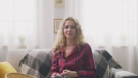 Ζουμ μέσα της συνεδρίασης γυναικών στον καναπέ, που πλέκει στο σπίτι και που φαίνεται κεκλεισμένων των θυρών φιλμ μικρού μήκους