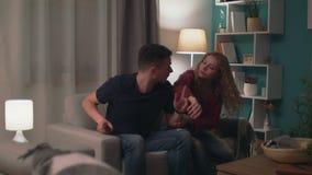 Ζουμ μέσα του άνδρα και της γυναίκας που παλεύουν για τη μακρινή TV στο καθιστικό στο βράδυ φιλμ μικρού μήκους