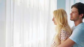 Ζουμ μέσα του νέου αγαπώντας ζεύγους που στέκεται μπροστά από το μεγάλο παράθυρο και το αγκάλιασμα φιλμ μικρού μήκους